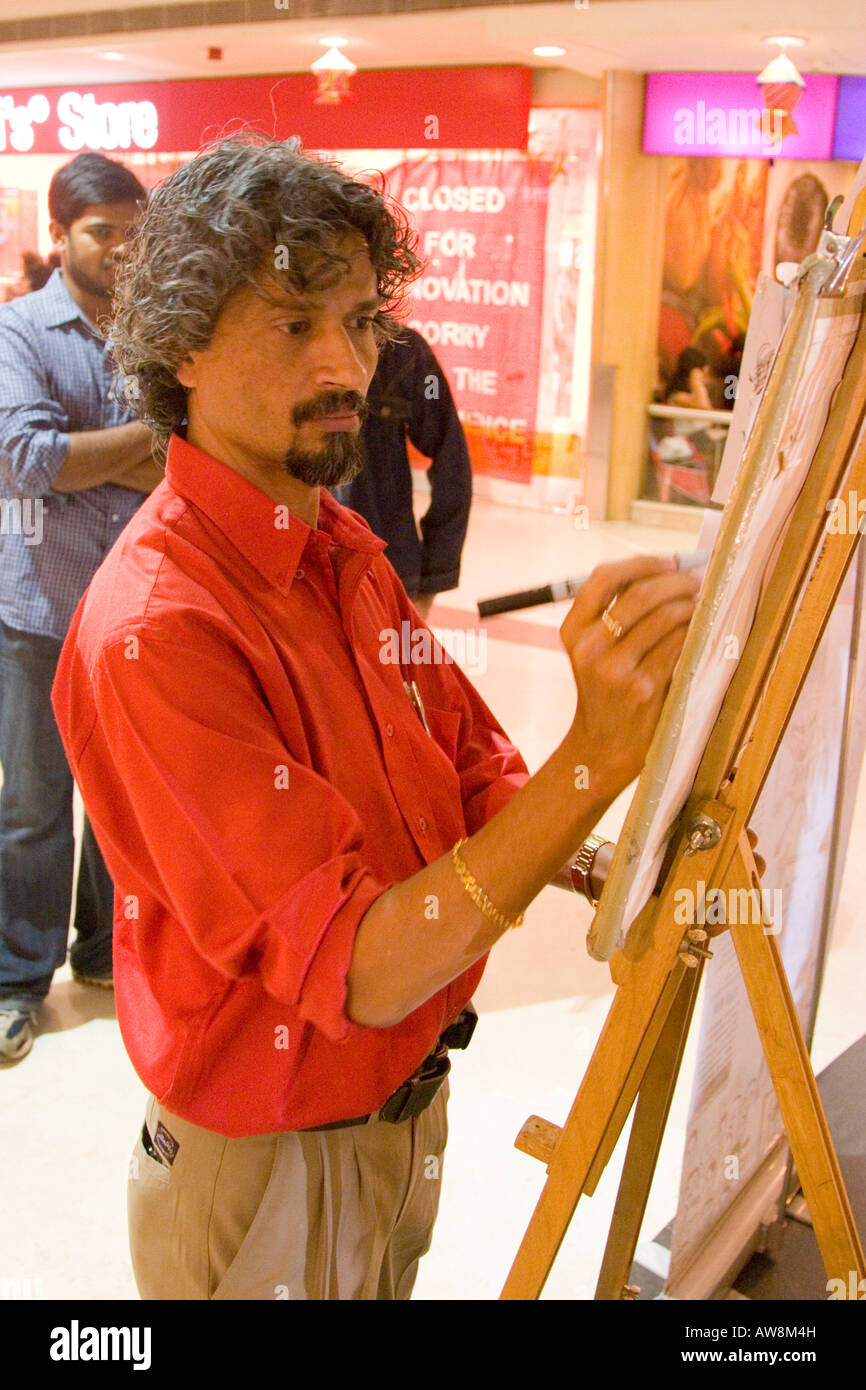 Man drawing caricatures inside a modern Indian shopping mall and shopping centre - Stock Image