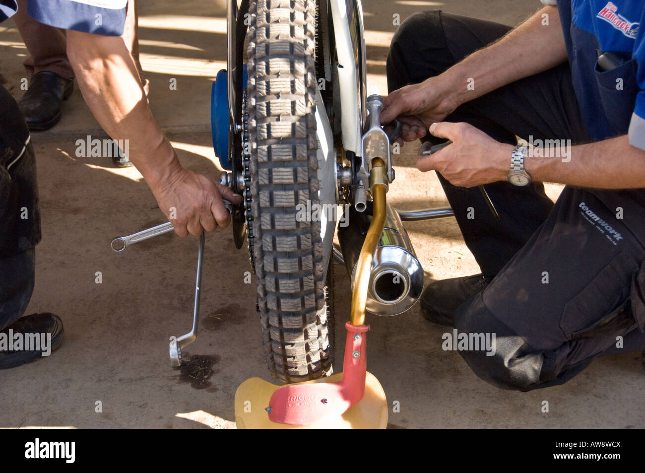 Mechanics working on a speedway motorcycle before a race - Stock Image