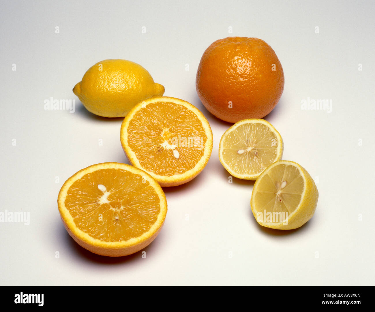 A whole orange and a whole lemon beside a lemon cut in half and an orange cut in half - Stock Image