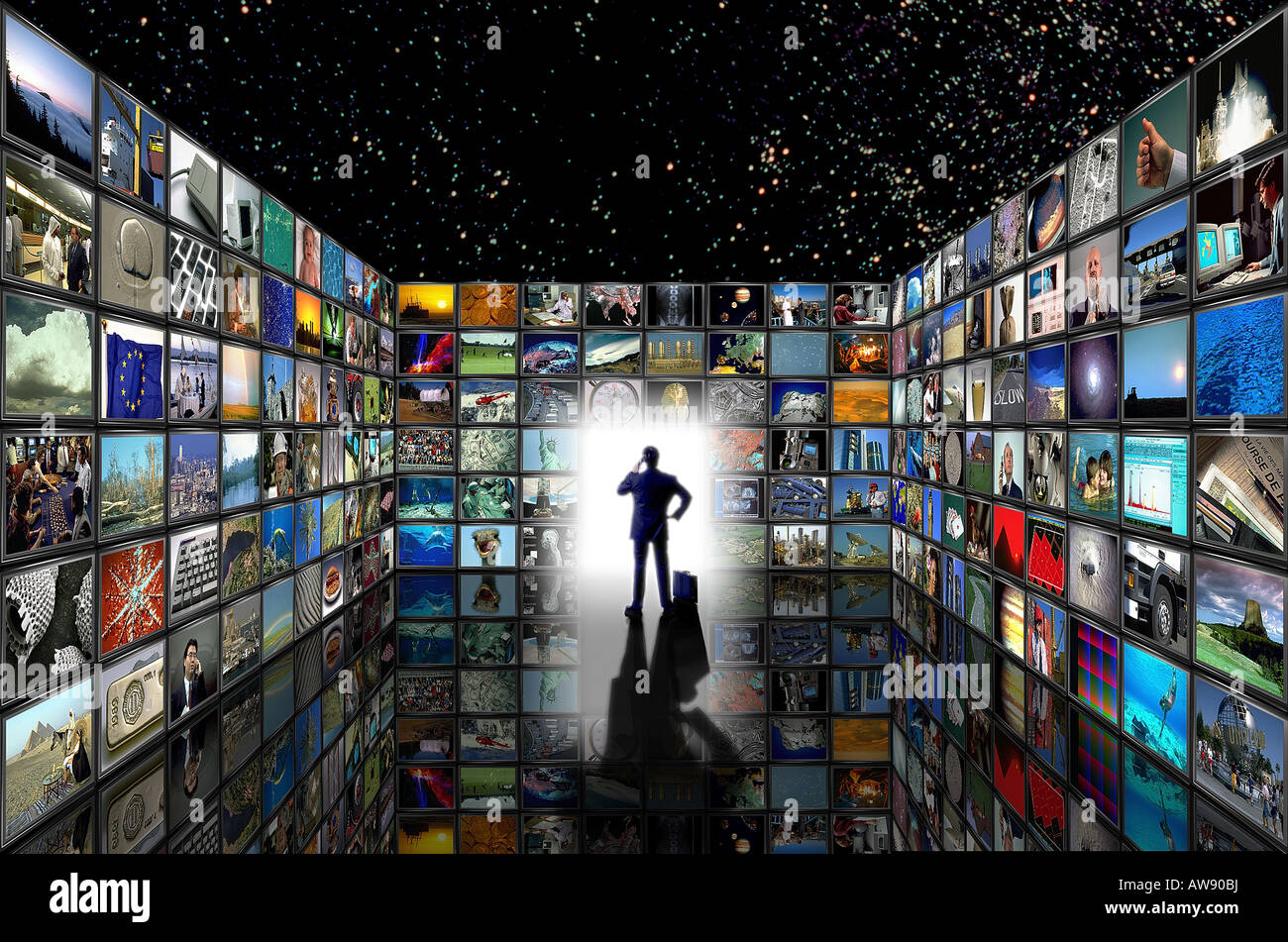 man in room of TV screens with many images - Stock Image
