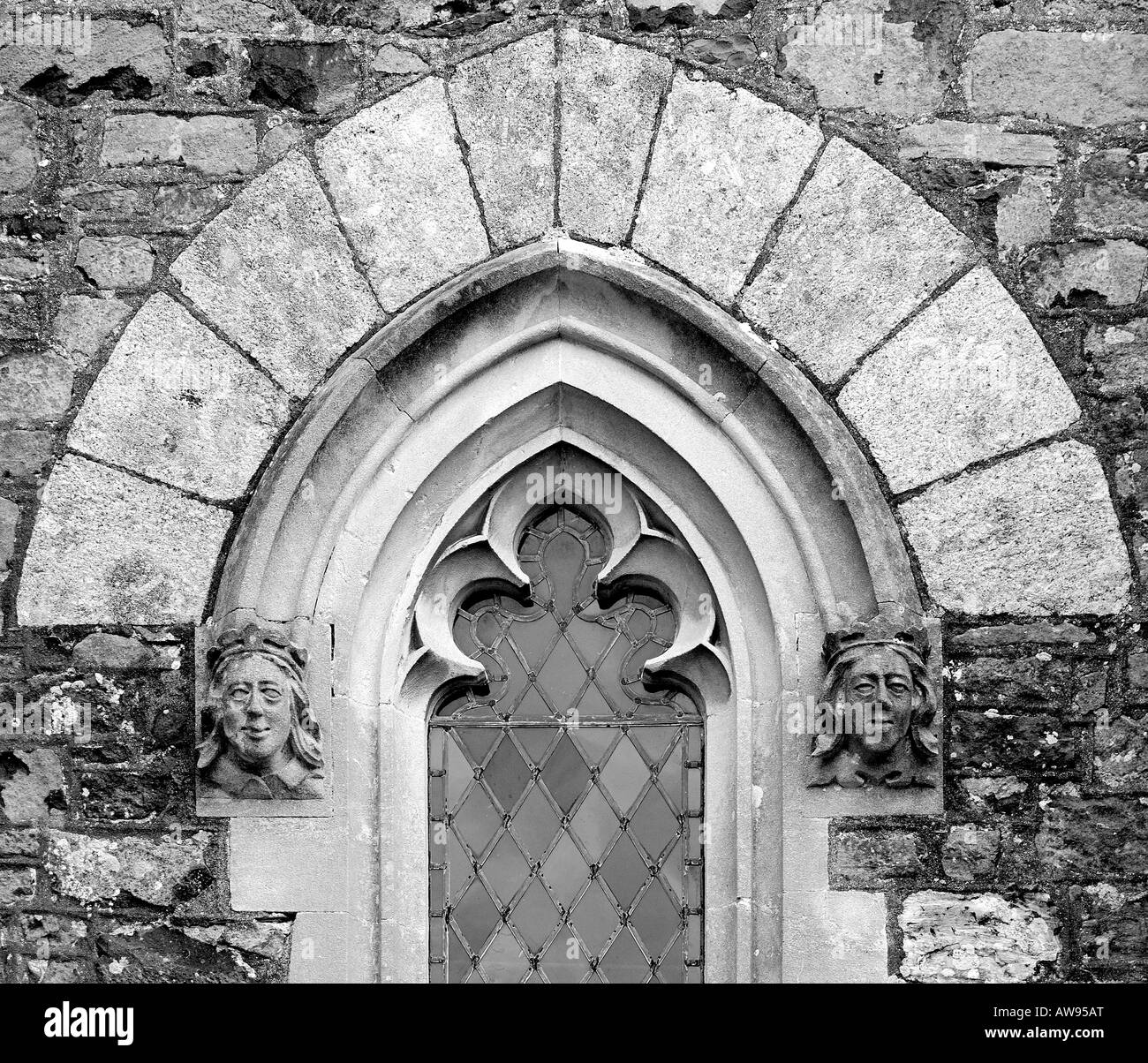 Architectural Detail Close Up Of A Gothic Arched Church Window With Stone Faces Each Side And Clear Leaded Glass In Monochrome