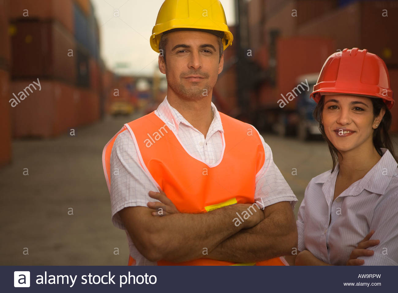 Portrait of two dock workers standing at a commercial dock and smiling - Stock Image