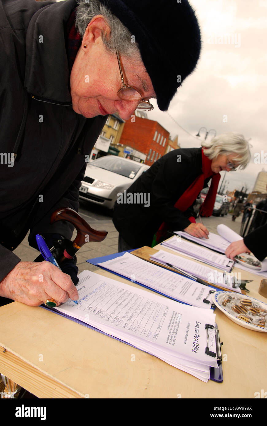 Members of the public signing a petition against possible closure of their local Post Office, High Street, New Malden, - Stock Image