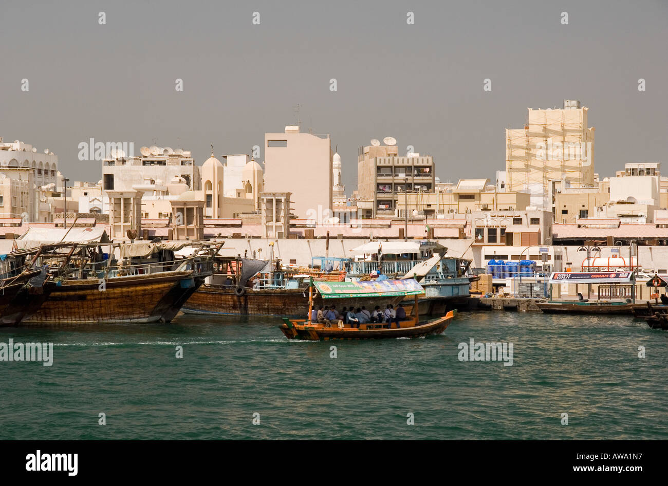 Deira shown from the Creek in Dubai, UAE. With small passenger ferry boats - abras, and the medium-sized freight carrying boats. - Stock Image