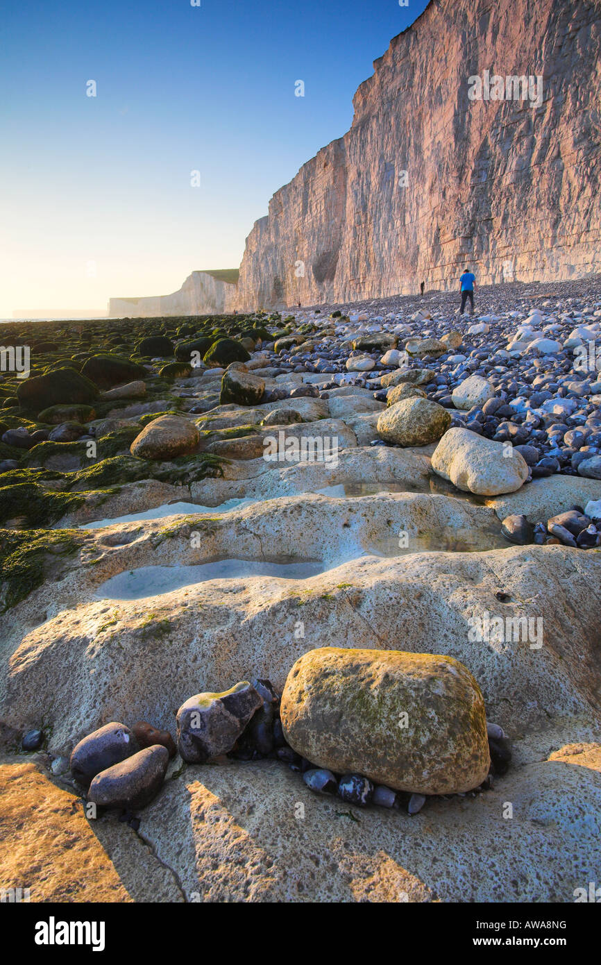 Holidaymakers wander the beach at Birling Gap looking for interesting pebbles, West Sussex - Stock Image