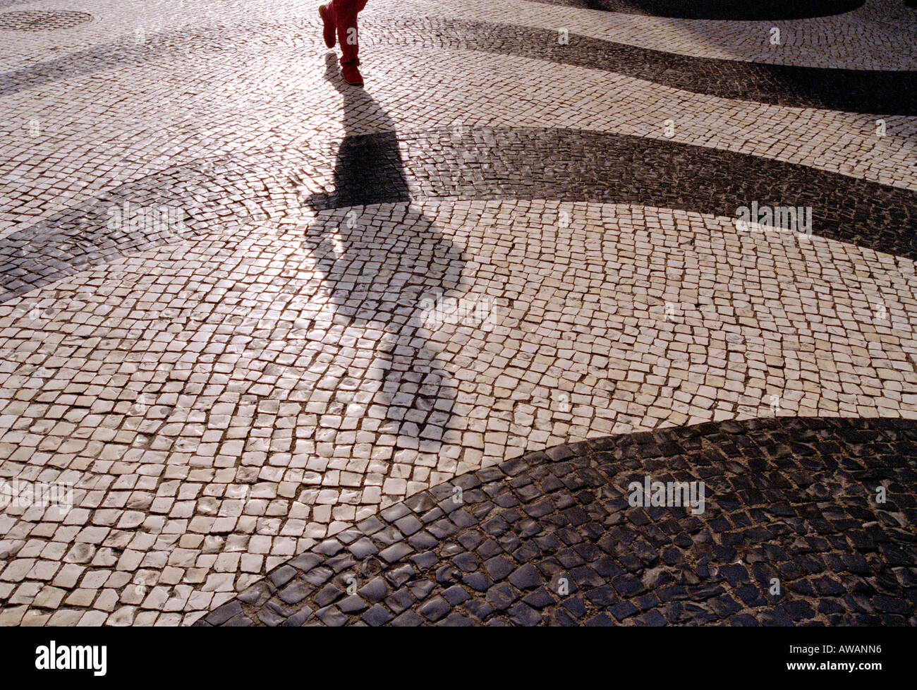 A mans feet and long shadow walking across a Mosaic Street, Largo de Santo Agostinho, Macau. - Stock Image