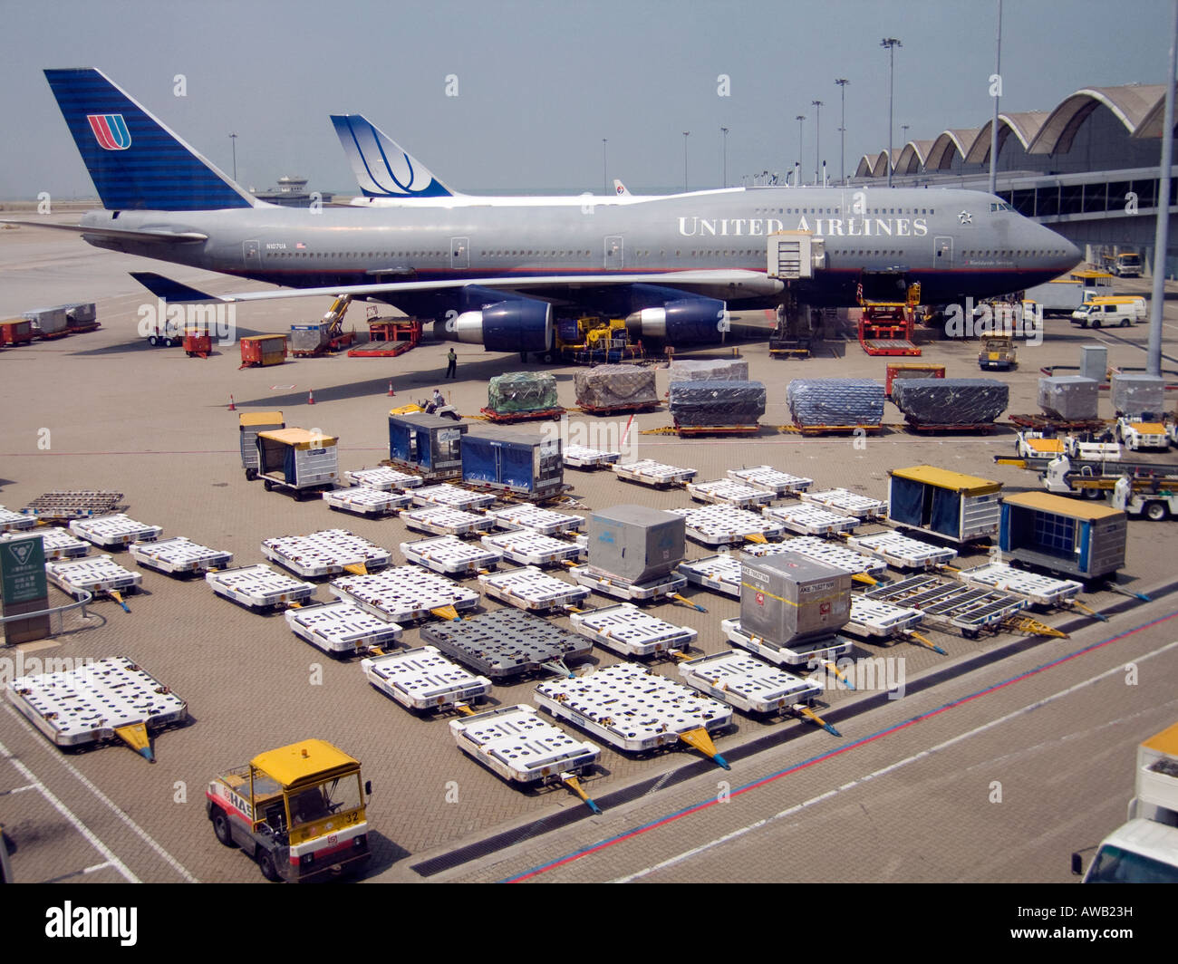 A commercial airplane docked at Hong Kong's Chek Lap Kok International Airport at  is ready for loading baggage - Stock Image