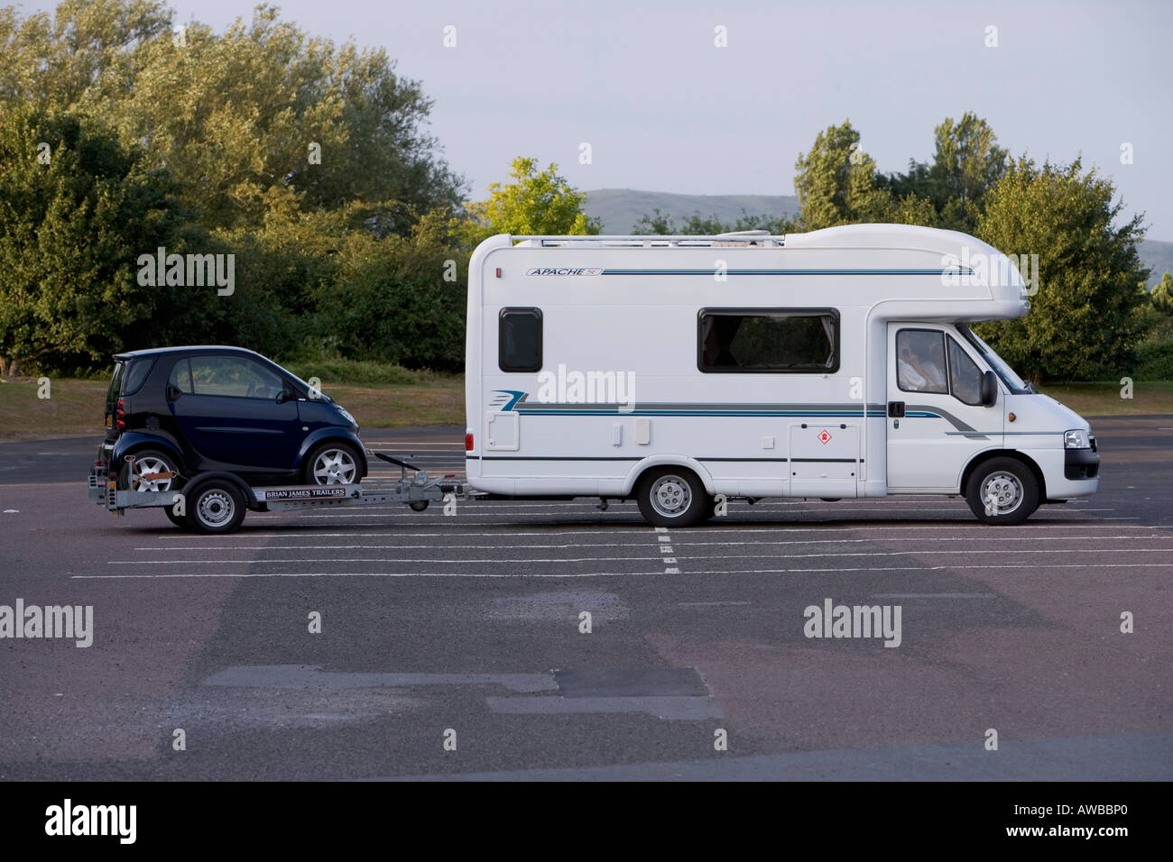 Motor home towing a Smart car on a trailer, parked in a M5 motorway services. - Stock Image