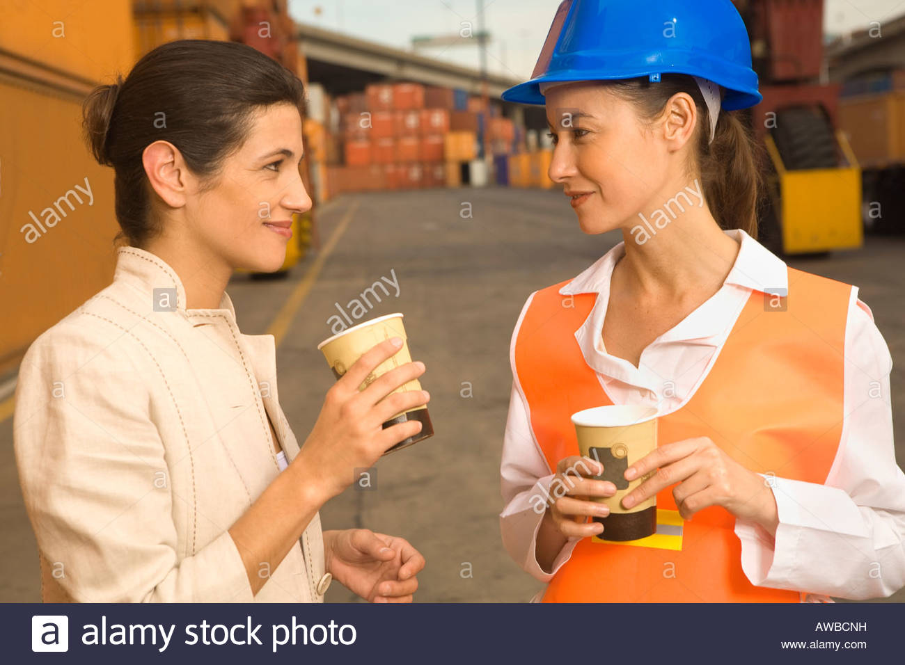 Two businesswomen holding disposable cups and talking - Stock Image