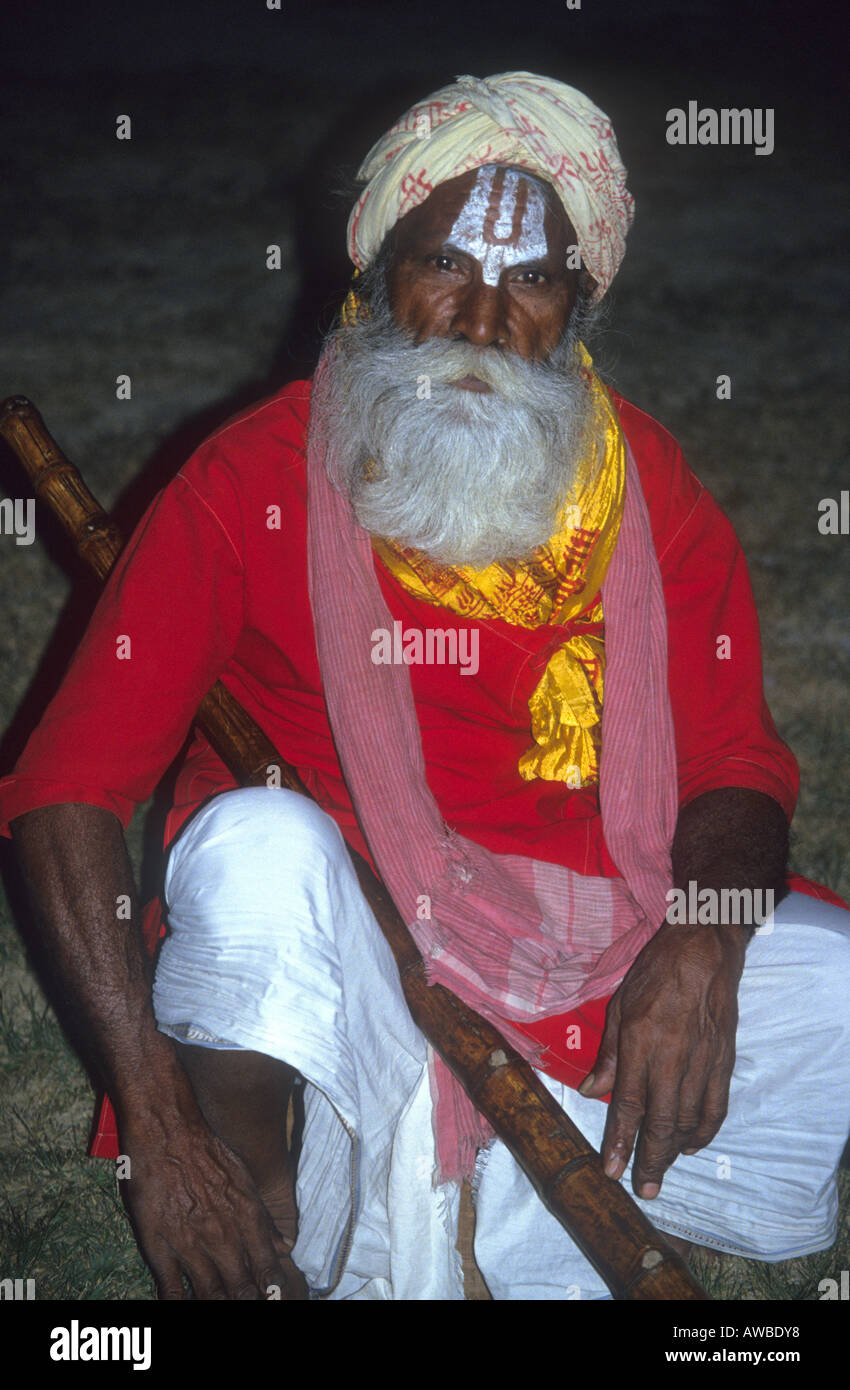 Red  robed Saddhu with painted face waiting for alms in India - Stock Image