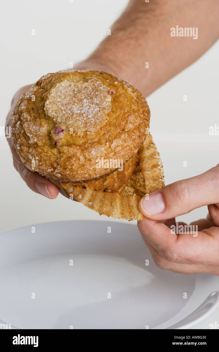 Hand peeling paper liner from muffin - Stock Image