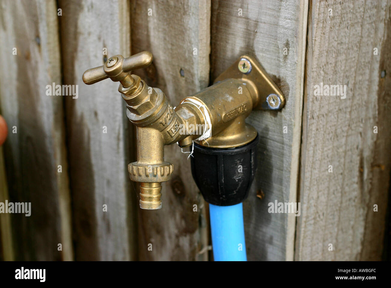 Attractive External Fresh Drinking Water Tap With Plastic Feed Pipe Fittings Mounted  On Outside Wooden Fence