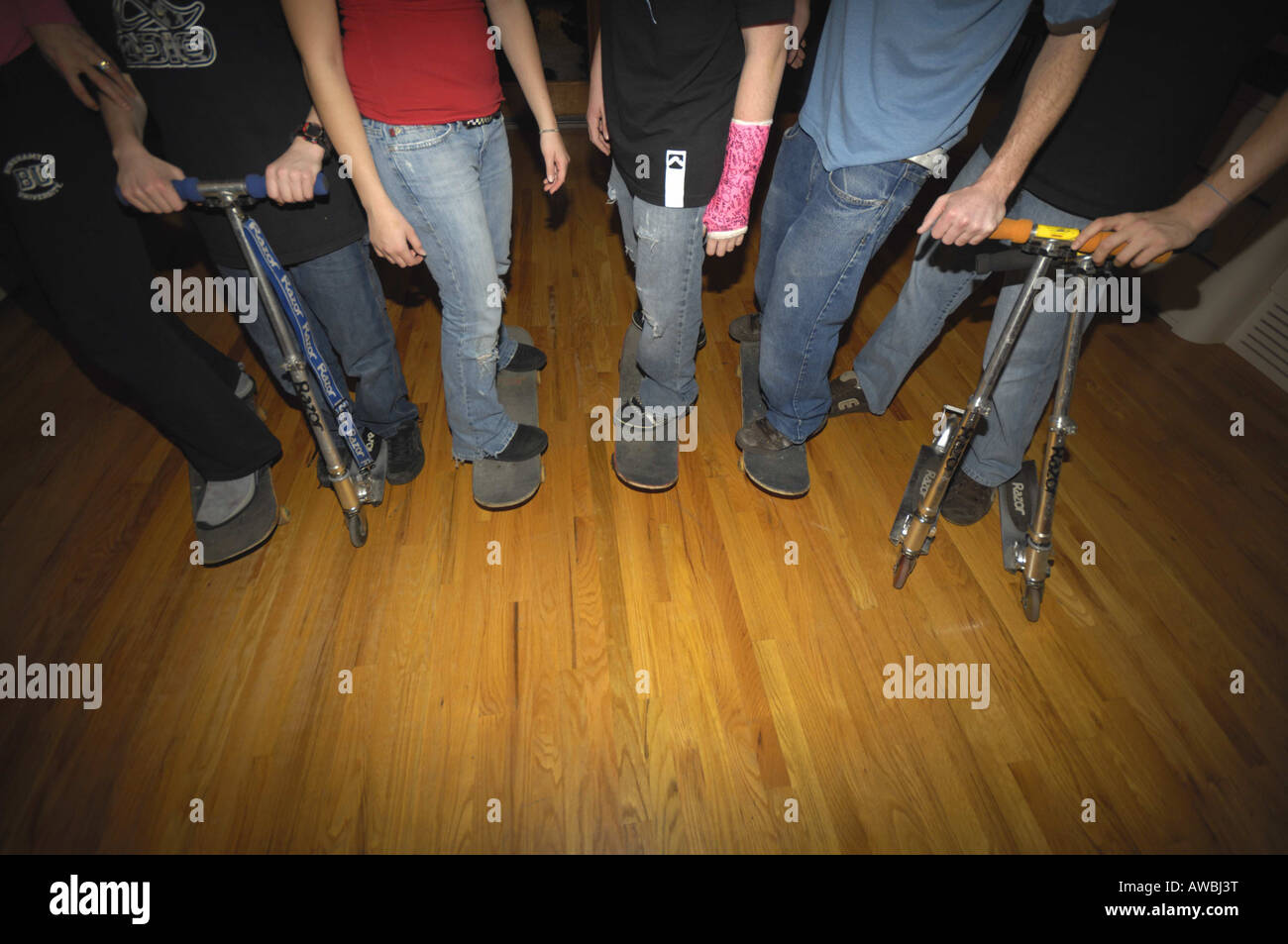 Teenagers standing on skateboards and skooters indoors Stock Photo