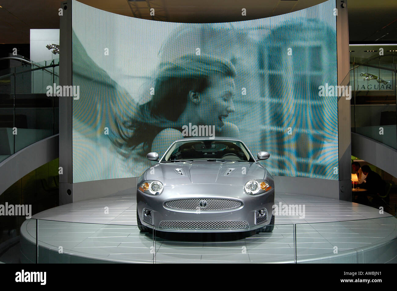 A new sleek car exhibited at the Paris International Auto Show, with an advertising movie appearing on the giant - Stock Image