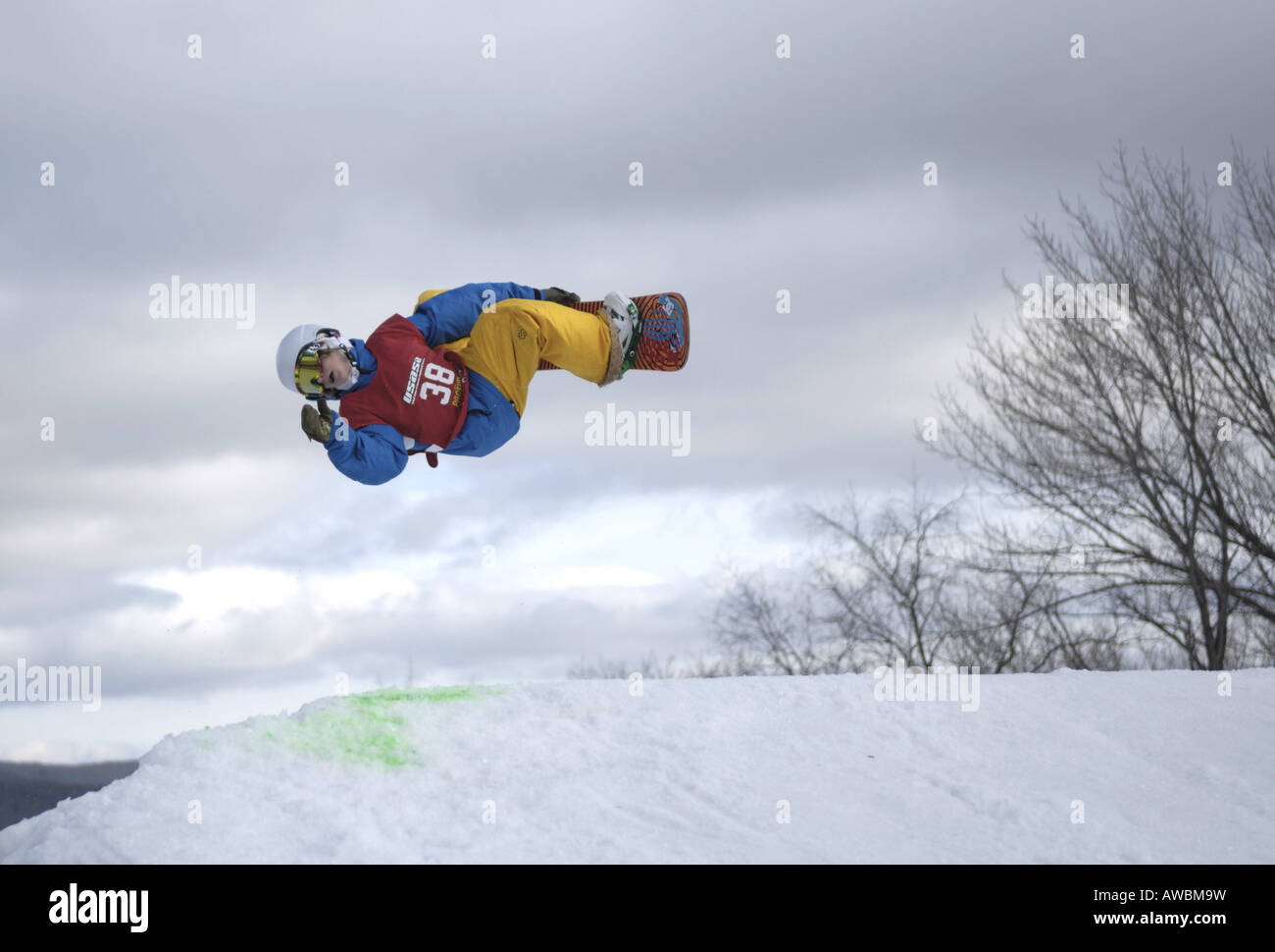 A young male snowboarder performs a freestyle mid air stunt - Stock Image