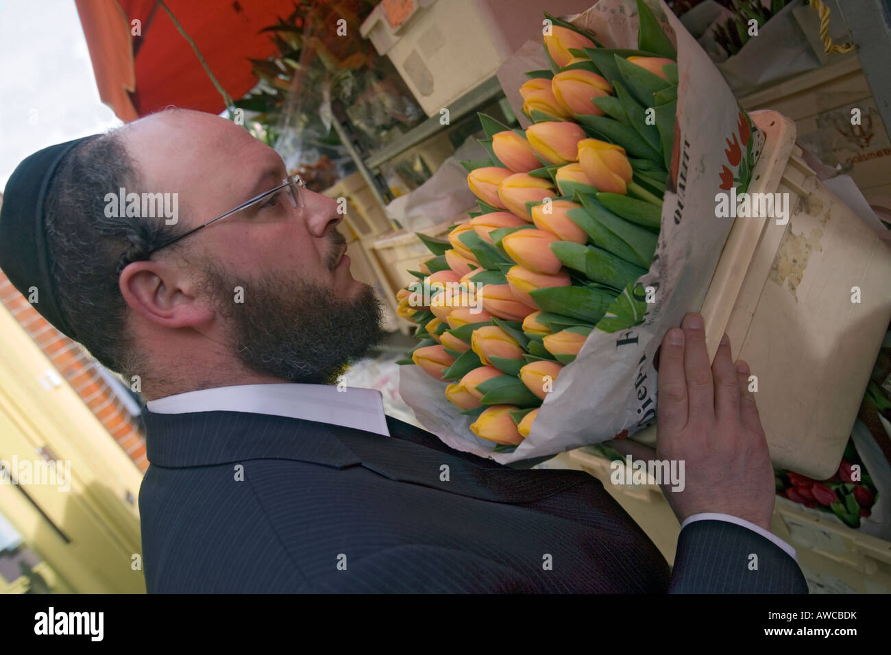 a jewish man smelling flowers at columbia road flower market - Stock Image