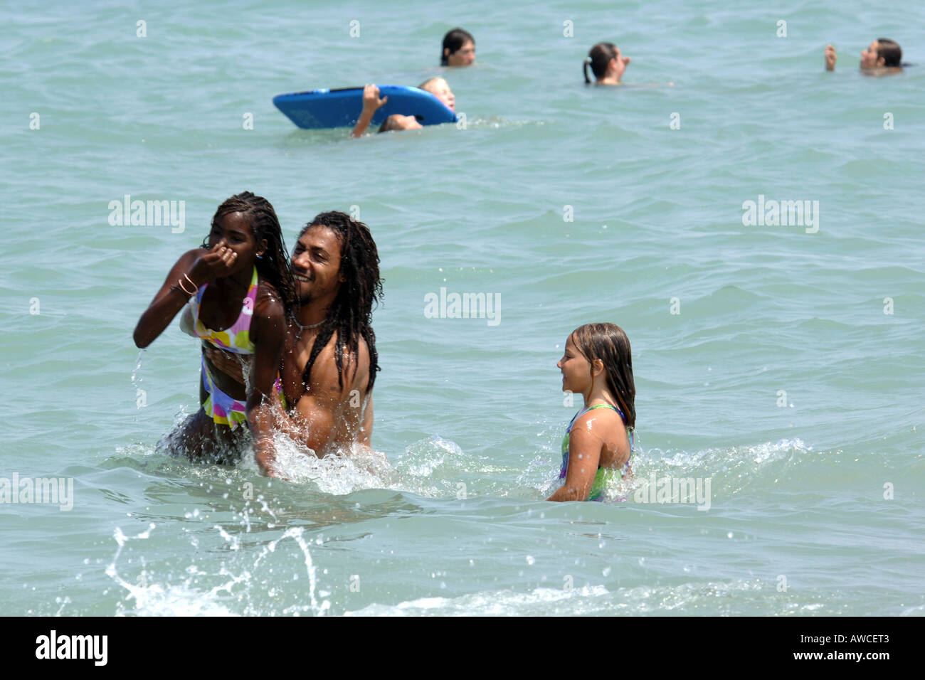 Ethnic Black Family At The Beach Having Fun In Sea Together On A Hot Summers Day