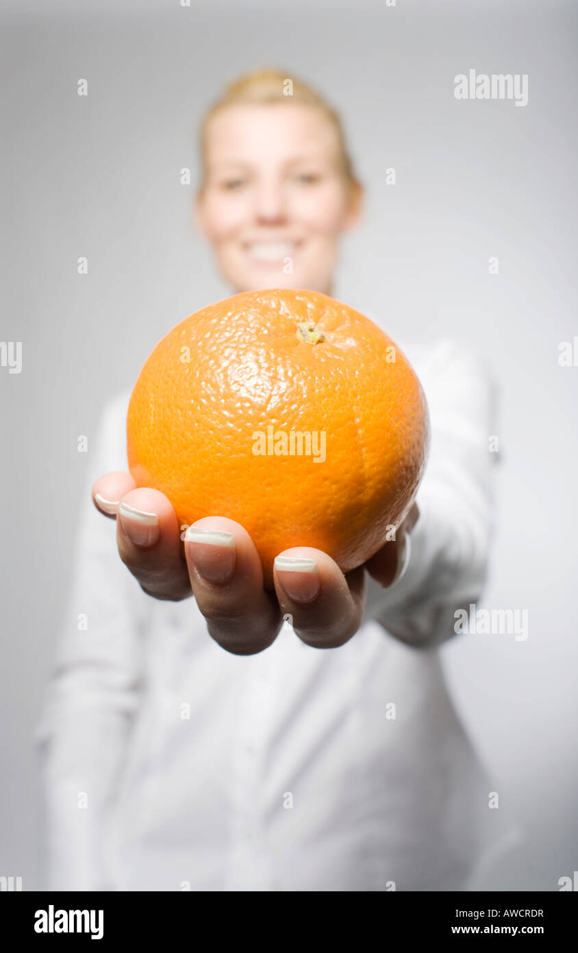 Blonde woman laughingly holding orange - Stock Image