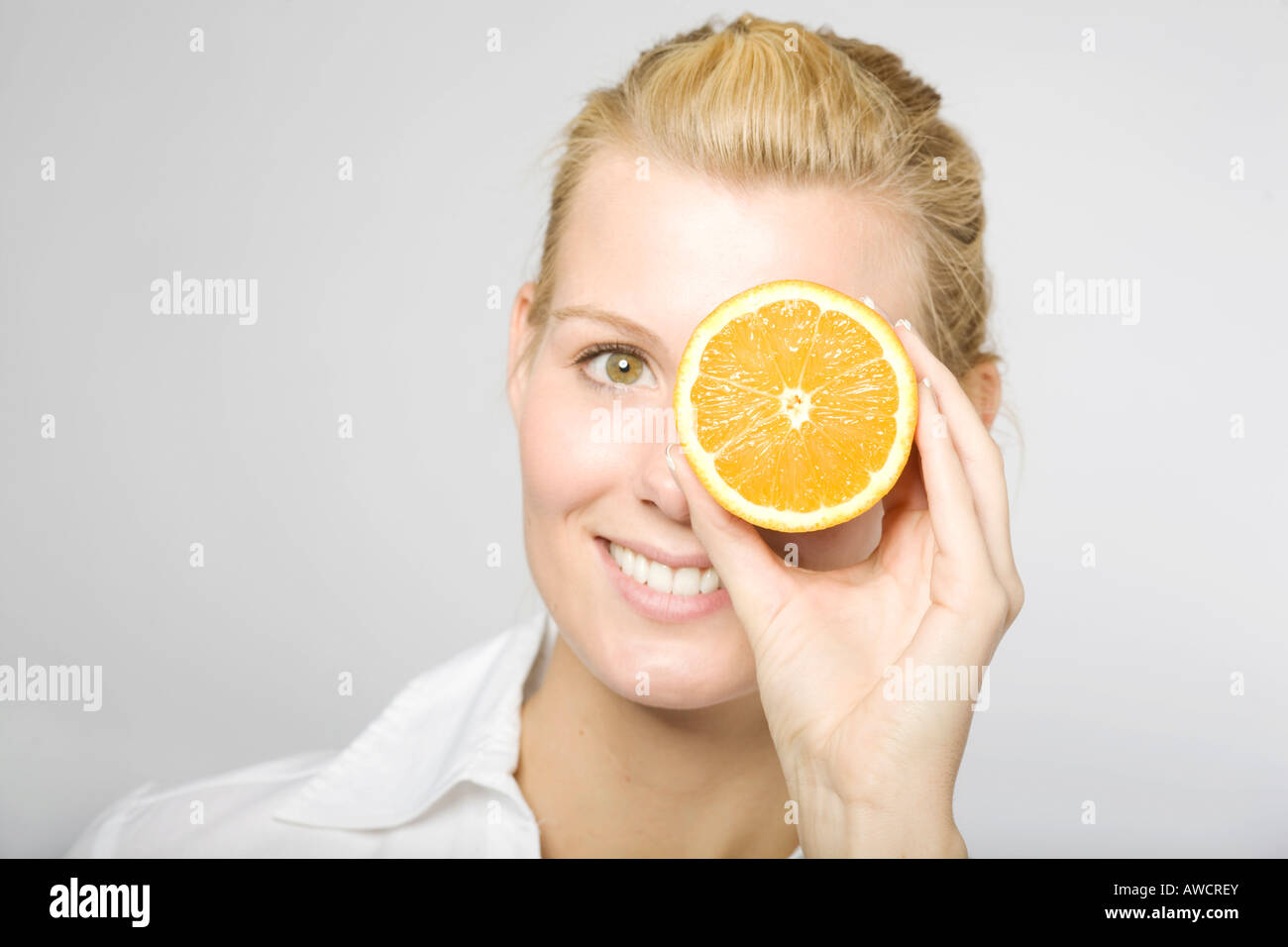 Blonde woman laughingly holding sliced orange in front of one eye - Stock Image