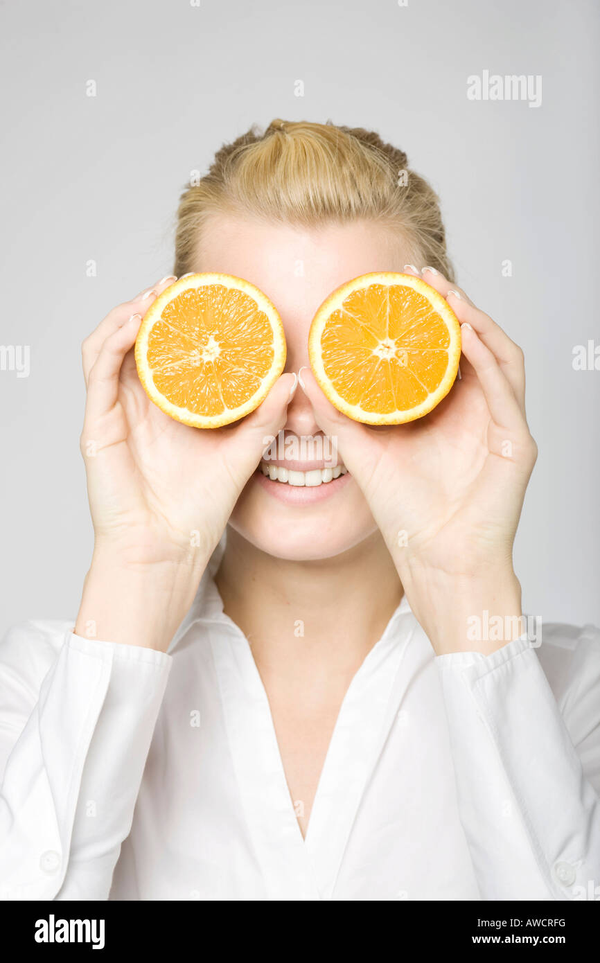 Blonde woman laughingly holding two sliced oranges in front of her eyes - Stock Image