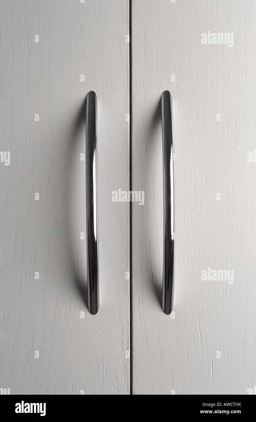 Pair of chrome door handles on white cupboard doors - Stock Image