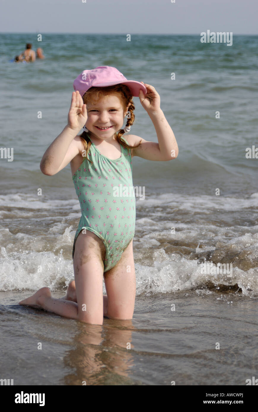 Little girl lies at a sandy beach at the sea - Stock Image