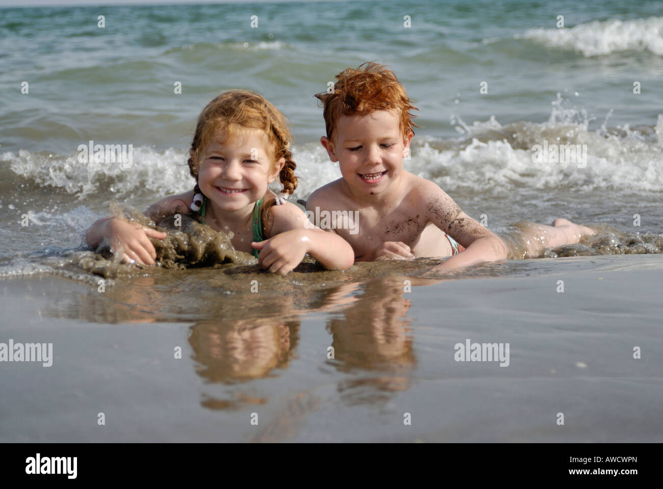 Two children are lying in the water at the beach and are having fun - Stock Image