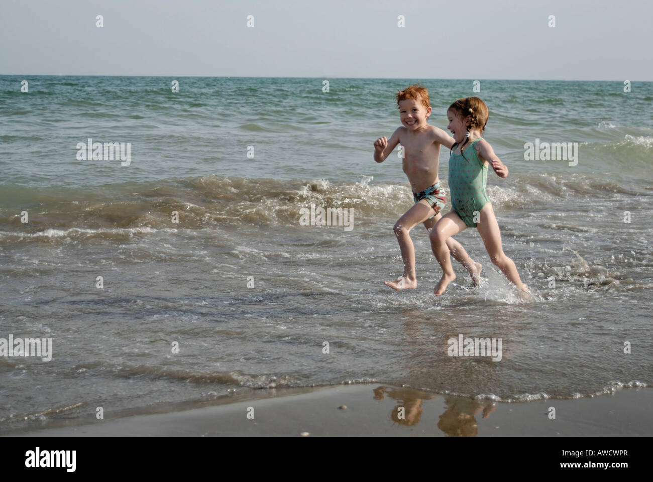 Mr two children are running at the beach - Stock Image