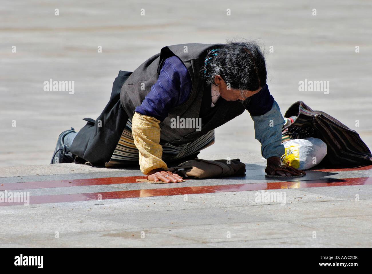 Female pilgrim, bending her body down to earth, Gyantse, Tibet - Stock Image