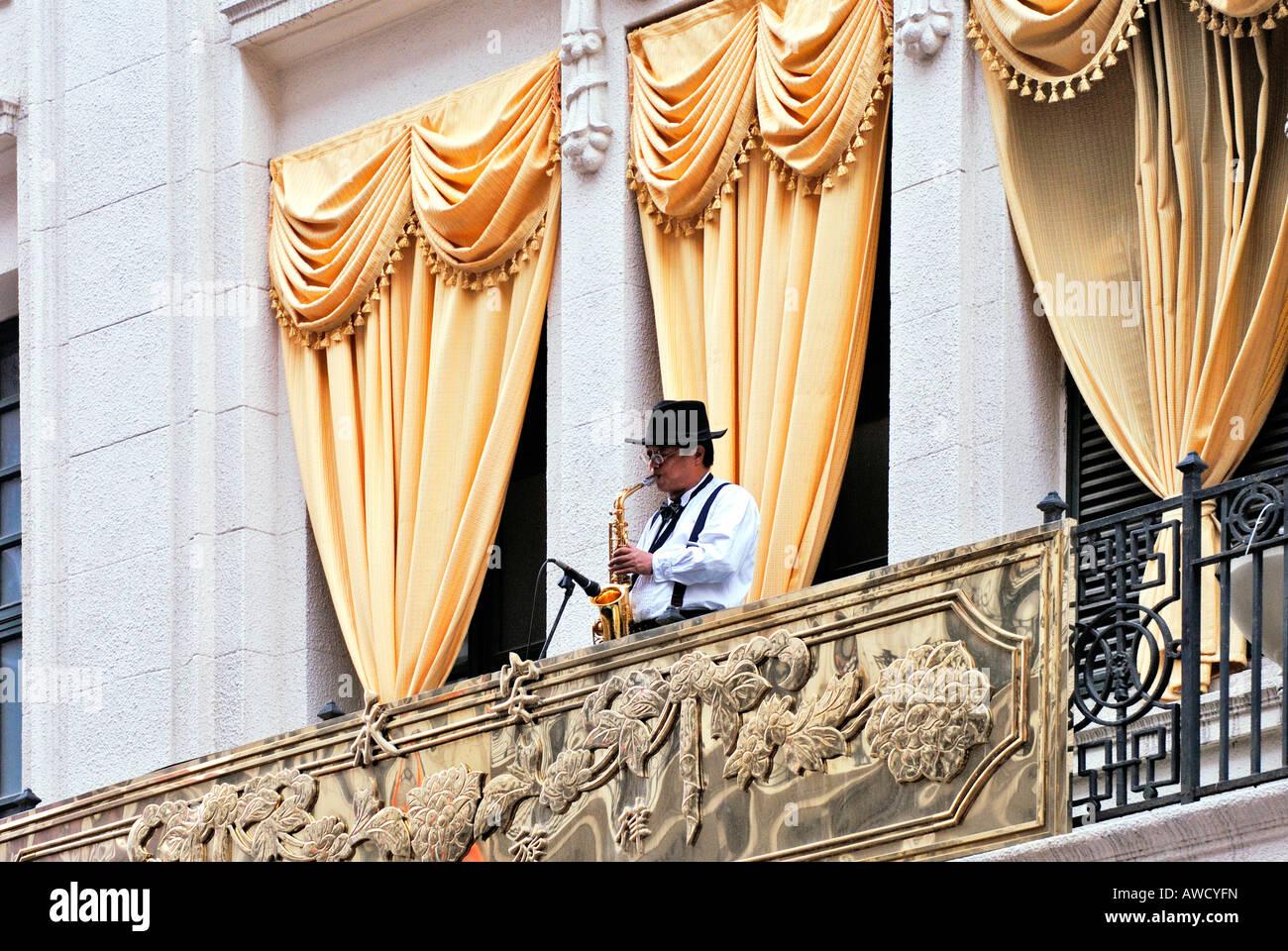 Man playing saxophone on a balkony, high street (Nanjing Donglu), Shanghai, China, Asia - Stock Image