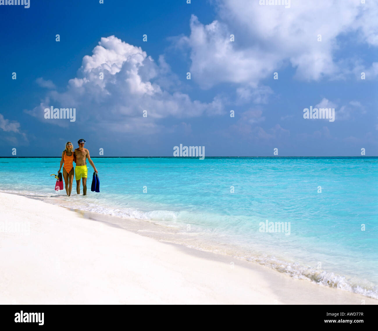 Young couple with snorkeling gear walking in shallow water, sandy beach, Maldives, Indian Ocean Stock Photo