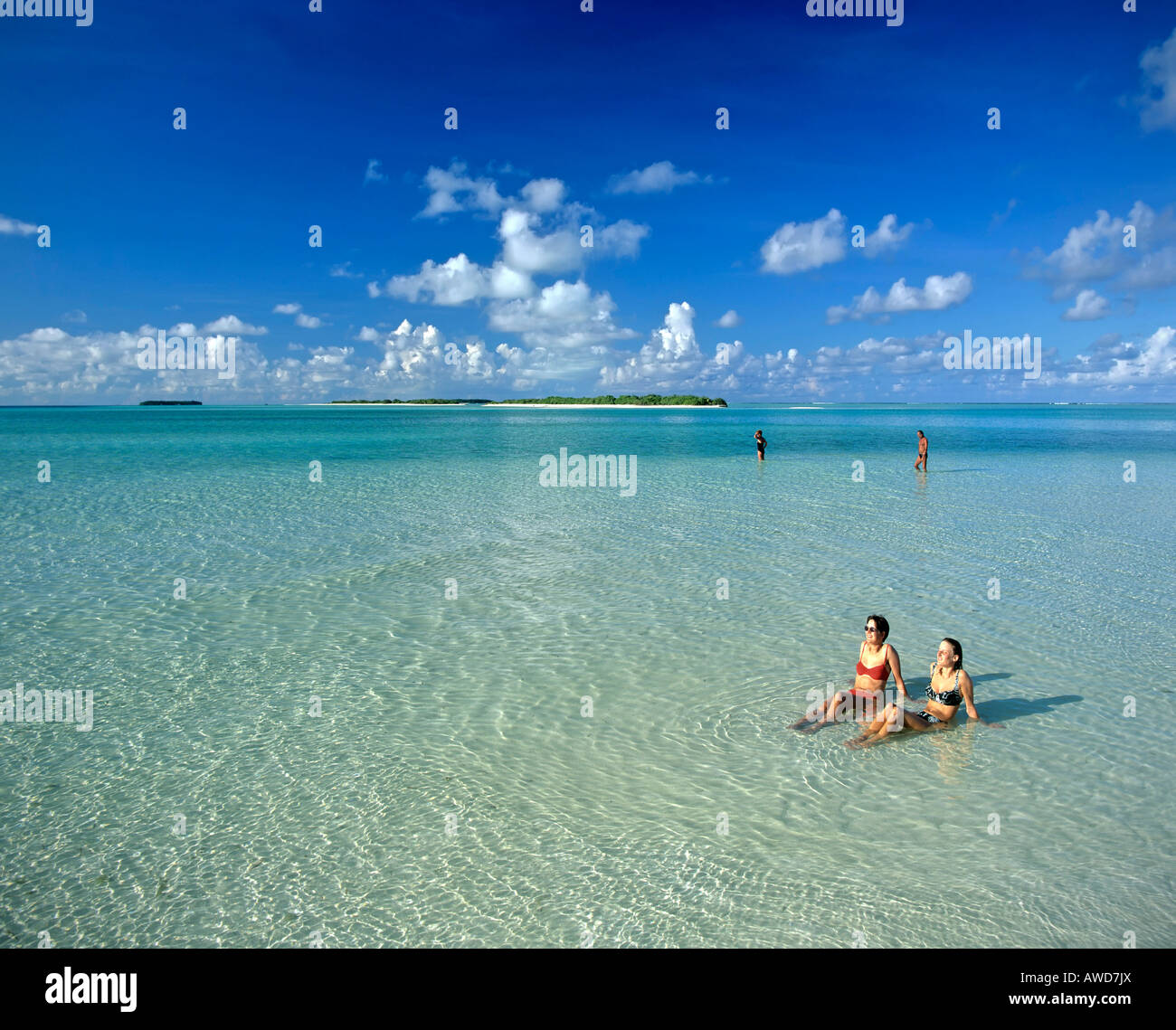 Young women relaxing in shallow water, island at the back, Maldives, Indian Ocean Stock Photo