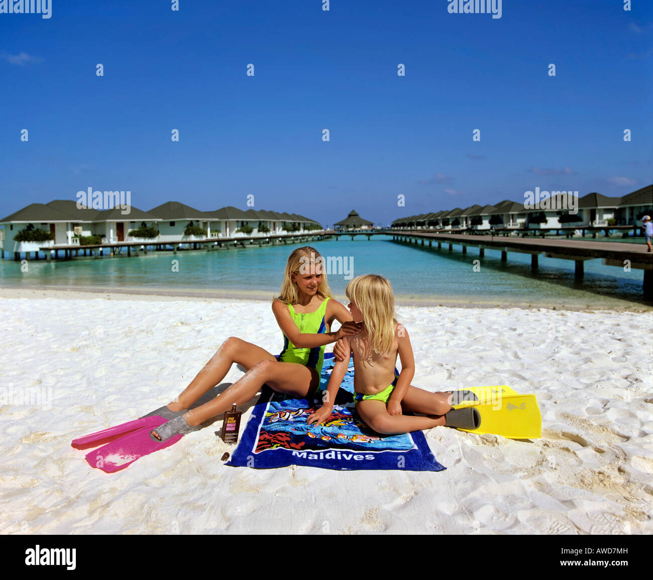 Young girls applying suntan lotion, sun protection, sunburn, water bungalows on Paradise Island, Lakanfinolhu, North - Stock Image