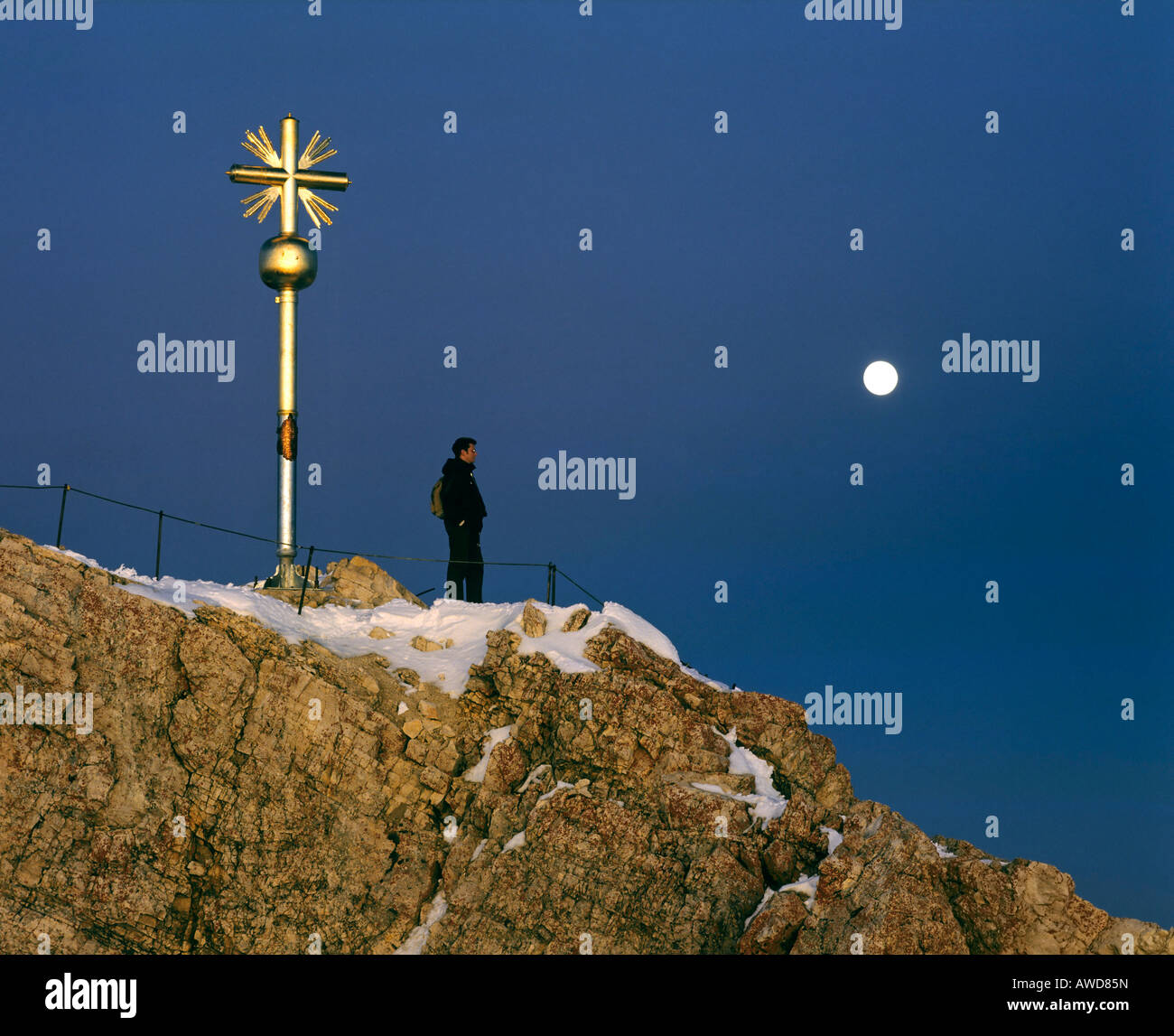 Summit cross at 2962 m or 9718 ft on the Zugspitze, Germany's highest mountain, at dusk, Wetterstein Range, - Stock Image