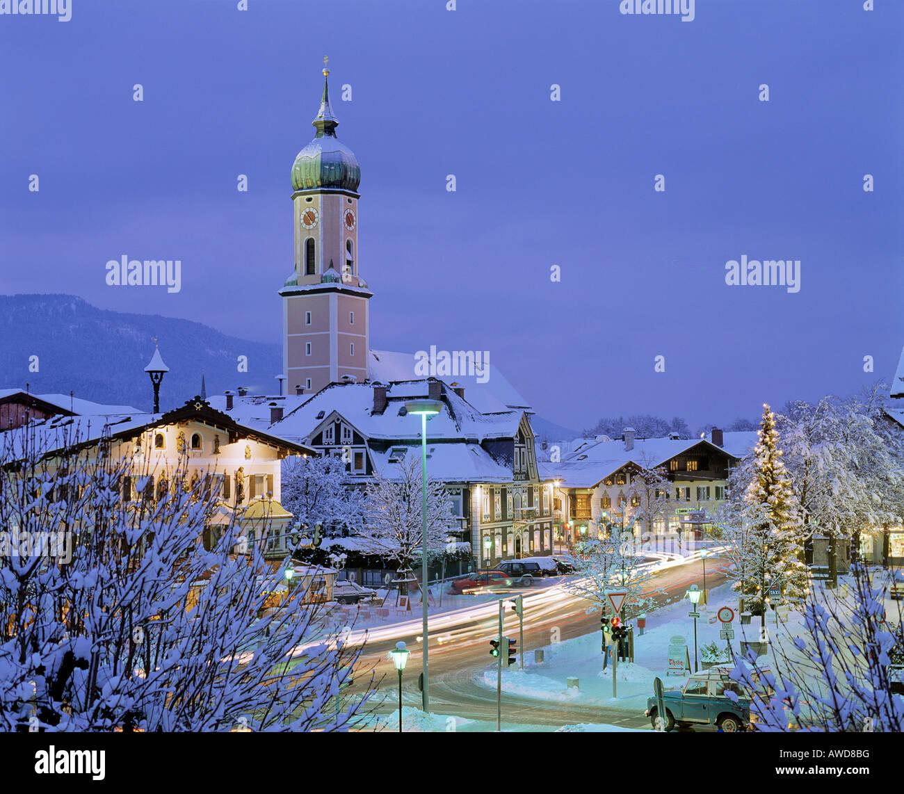 Church in Garmisch-Partenkirchen at dusk, Christmastime, Christmas tree in town square, Upper Bavaria, Bavaria, - Stock Image