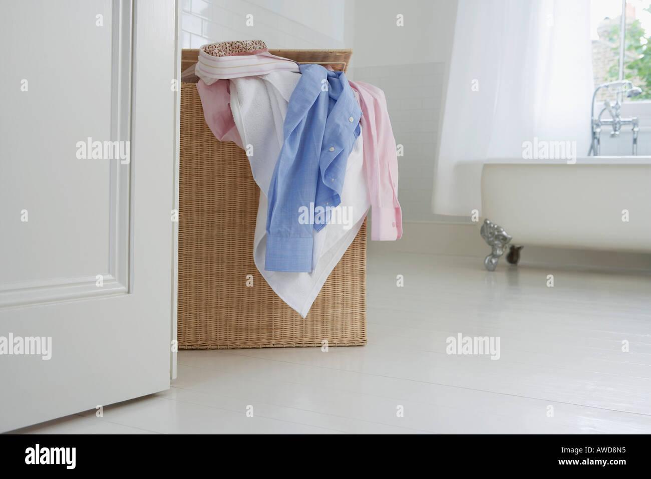 Overflowing laundry basket in bathroom - Stock Image