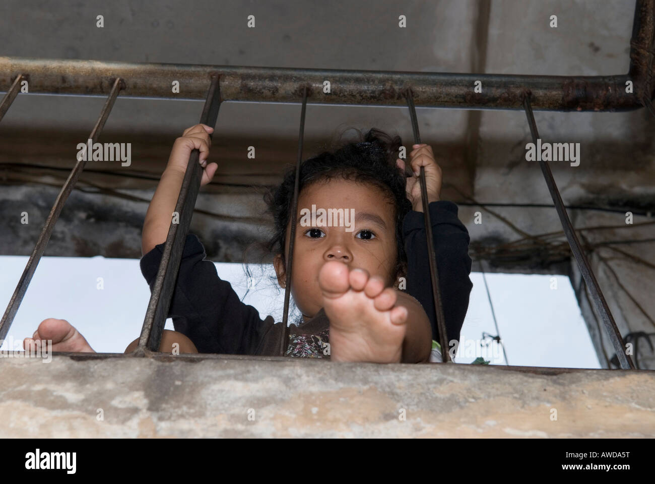 Girl at the bannister in the staircase of an appartment block, Dey Krahom slum area, Phnom Phen, Cambodia Stock Photo