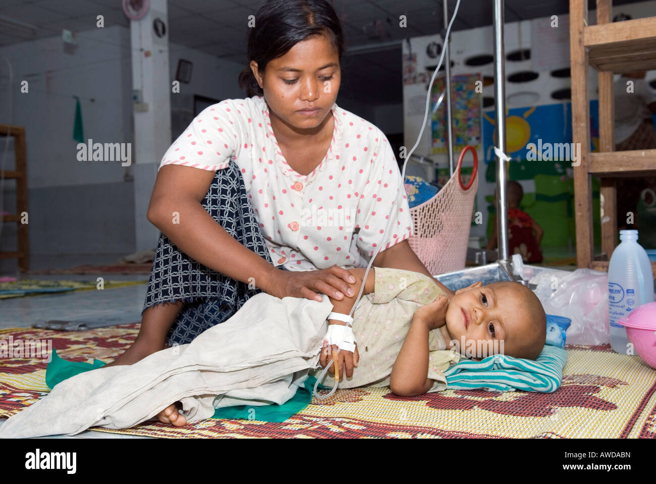 Burmese refugee mother caring about her sick child, paediatric station, Mae Tao Clinic, Maesot, Thailand - Stock Image