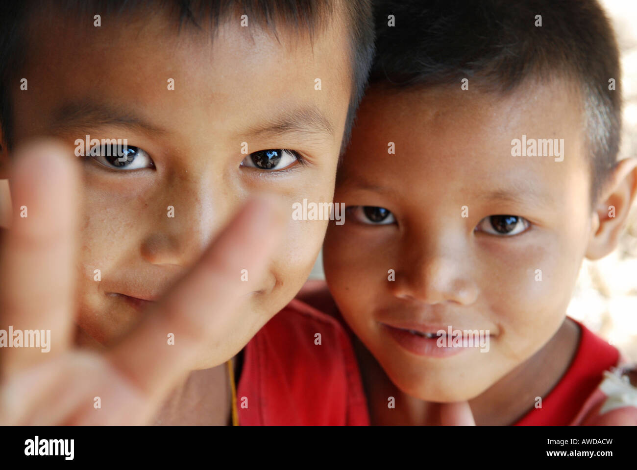 Boys showing victory salute, Kyunt Phan village, IDP-Area bordering Thailand near Maesot, Birma - Stock Image