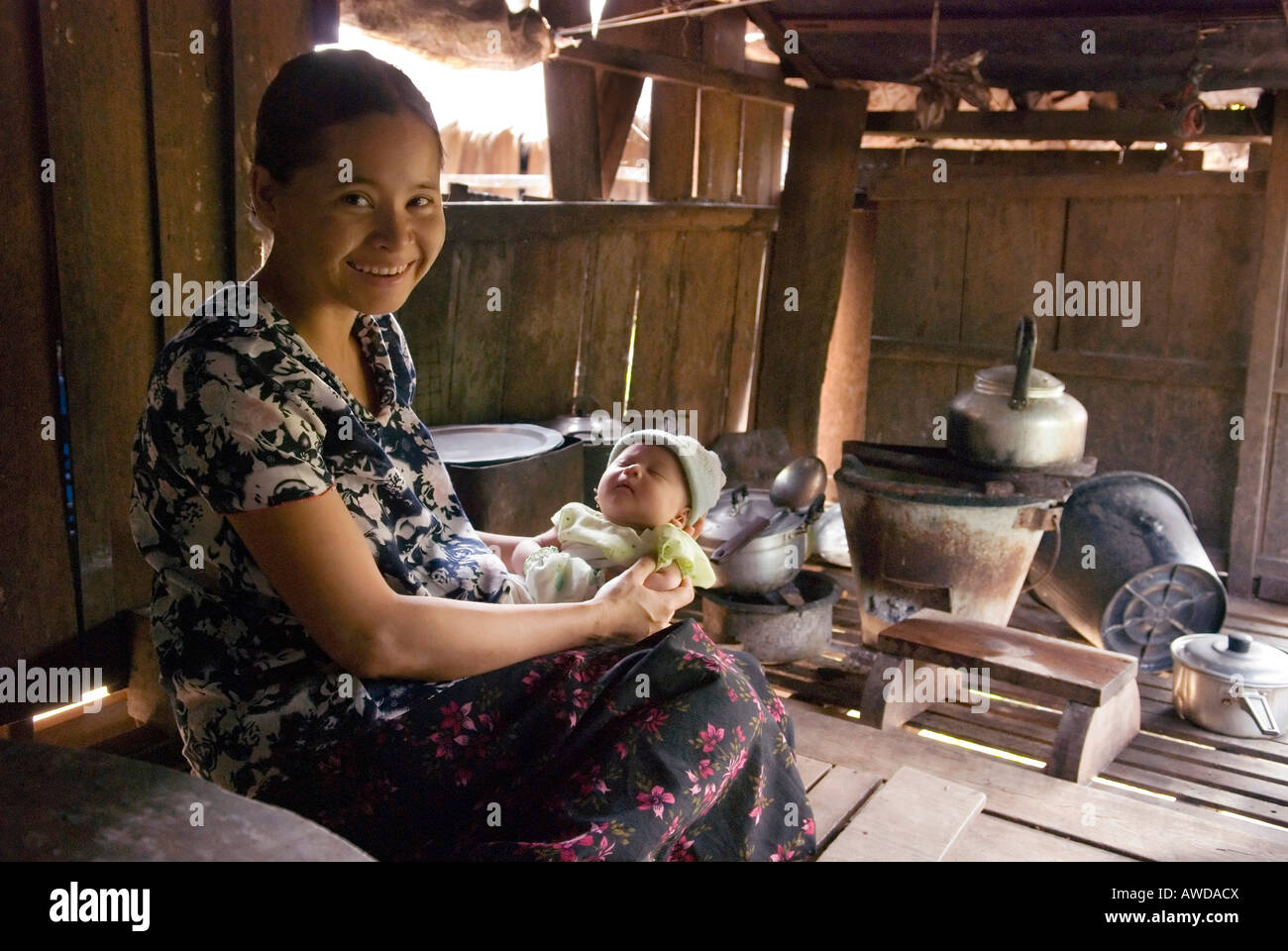 Mother with child in a simple kitchen, Kway Nya Ou village, IDP-Area bordering Thailand near Maesot, Birma - Stock Image
