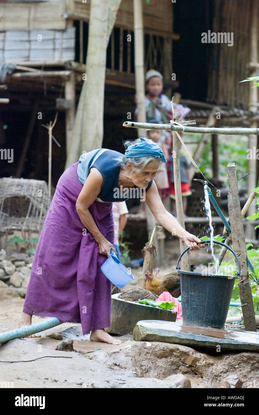 Old woman collecting water at the source, refugee camp Ei Tu Hta, IDP-Area bordering Thailand near Mae Sariang, - Stock Image