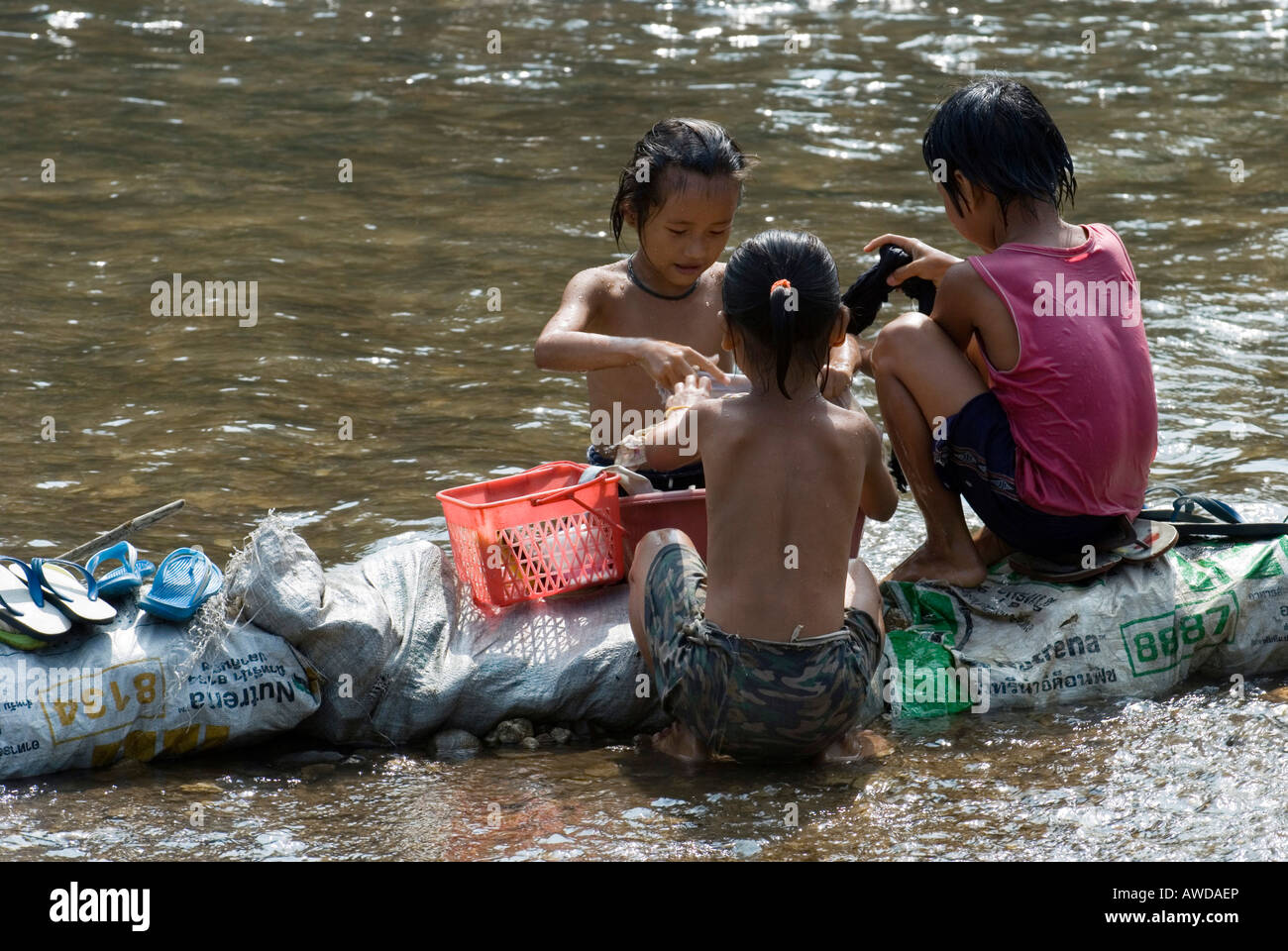 Children washing clothes in the river, Mae Ra Camp for Burmese refugees, Maesot, Thailand - Stock Image