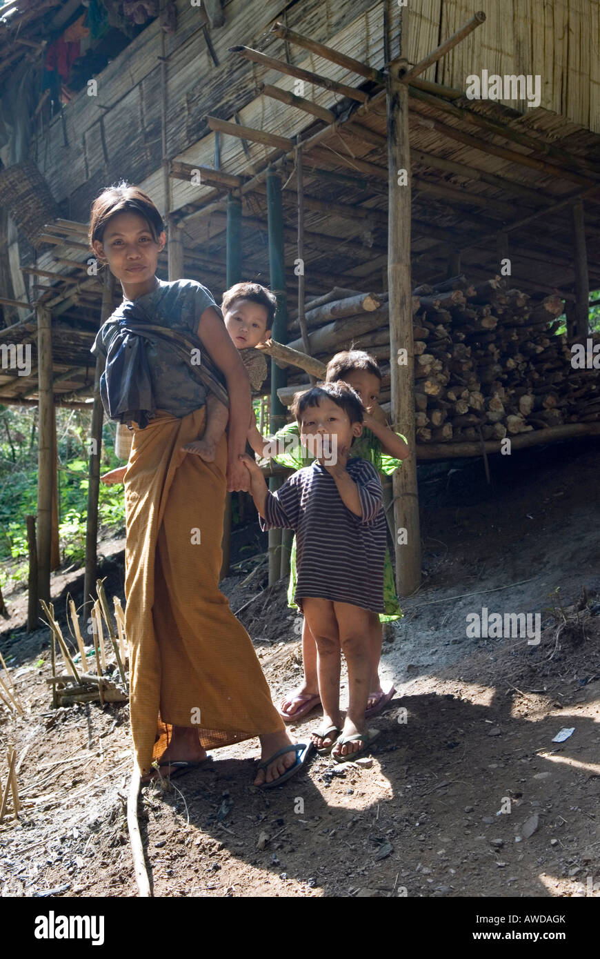 Refugee woman with children infront of a traditional stilt house, refugee camp Oh Win Hta, IDP-Area bordering Thailand - Stock Image