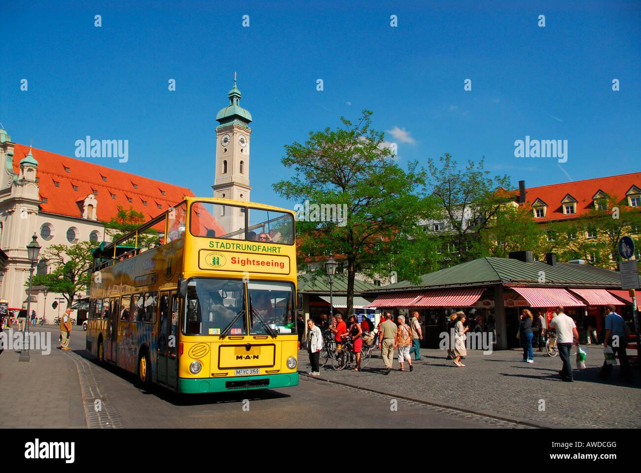 Tourist bus in front of Holy Ghost Church (Heilig-Geist-Kirche) at Viktualienmarkt, Munich, Bavaria, Germany Stock Photo