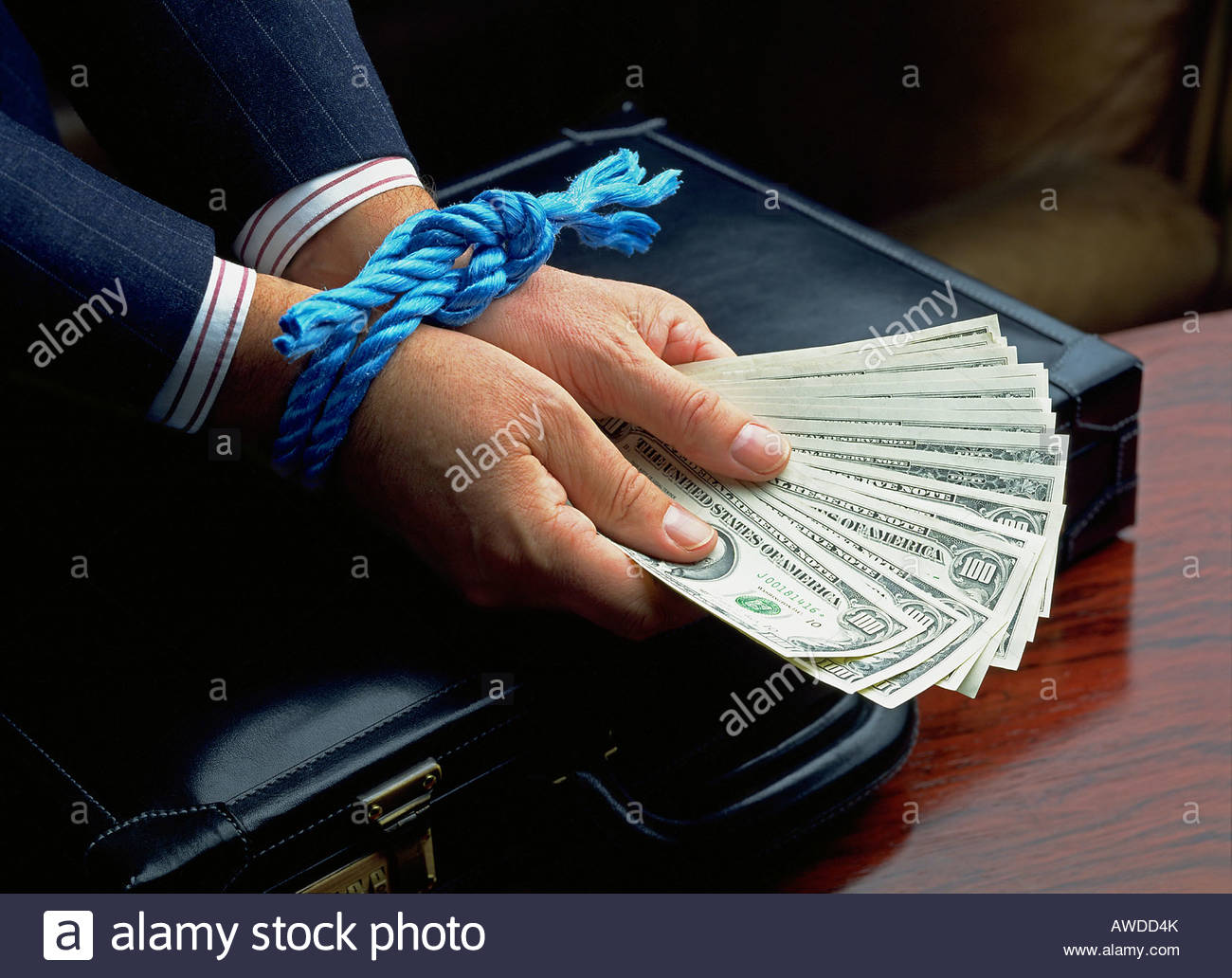 Man with wrists tied holding dollars - Stock Image
