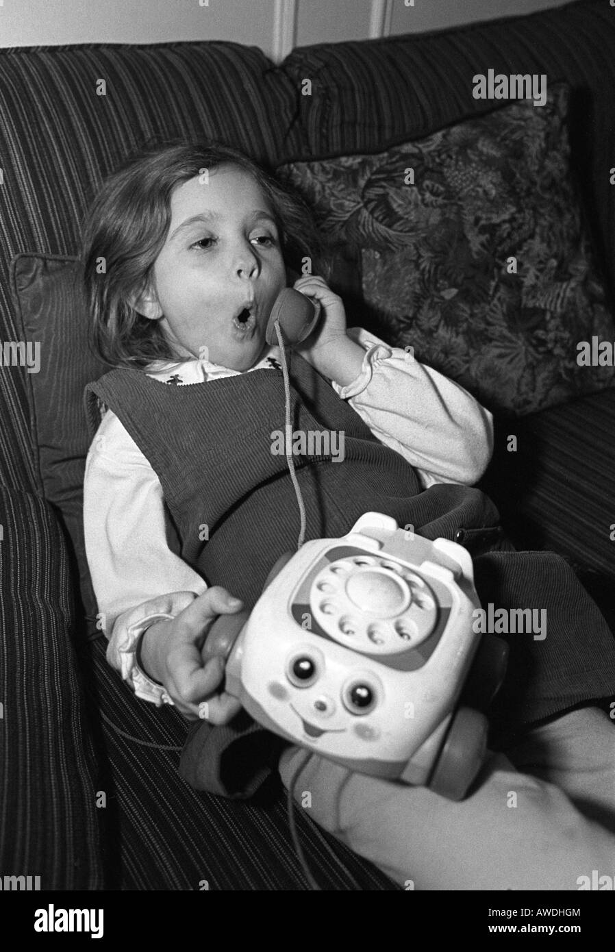 Young girl having quite a conversation on her toy phone - Stock Image
