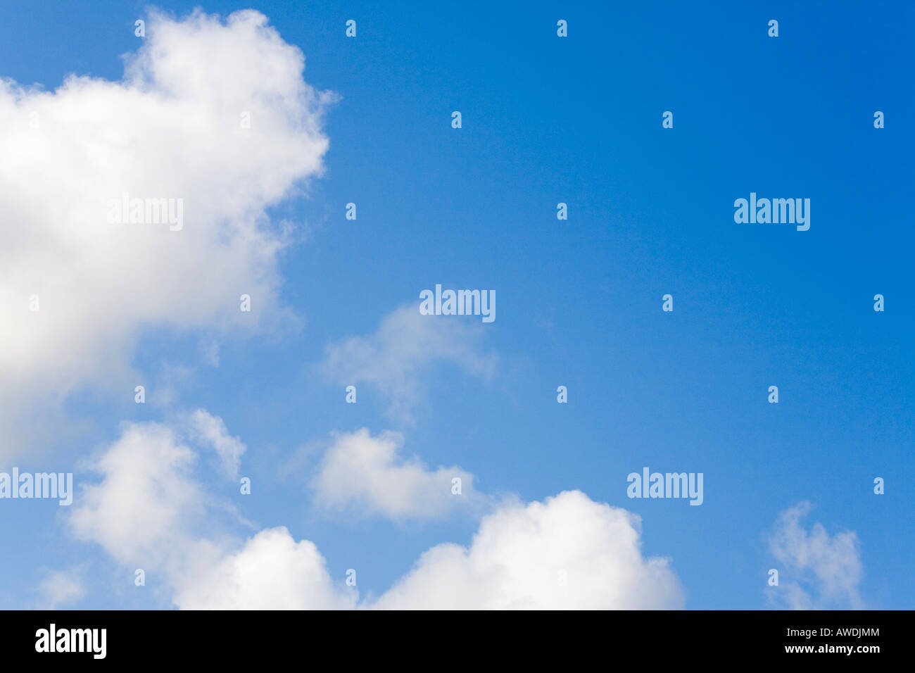 Fluffy white cumulus clouds in a blue sky indicating clement summer weather. England UK Britain - Stock Image