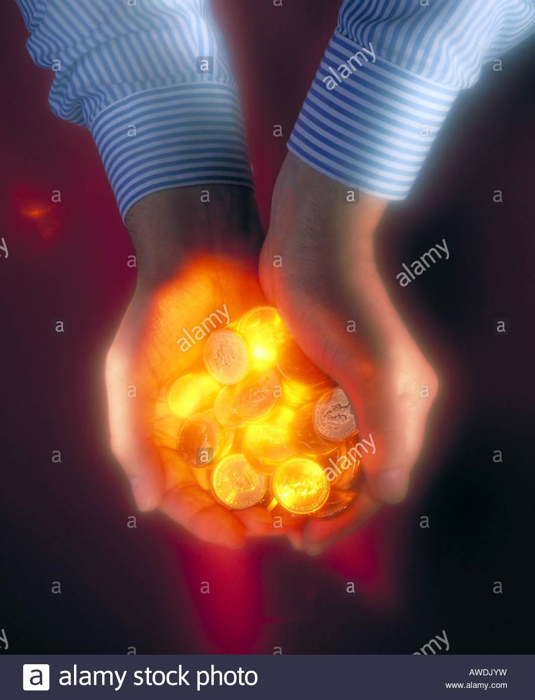 Hands holding hot golden money - Stock Image