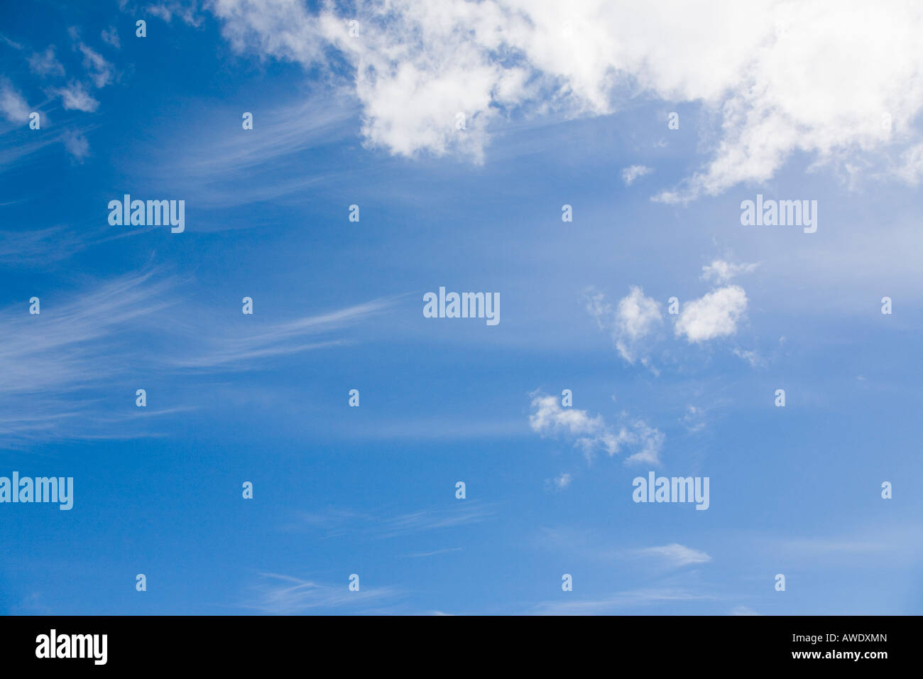 Blue sky with fluffy white cumulus clouds and cirrus mare's tail cloud in clement weather. England UK Britain - Stock Image