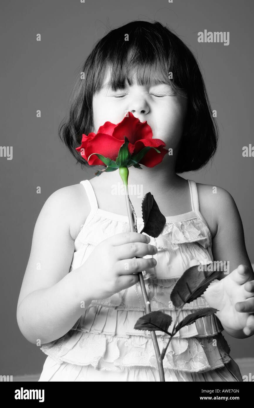 Child 3 year old girl smelling red rose black and white red rose